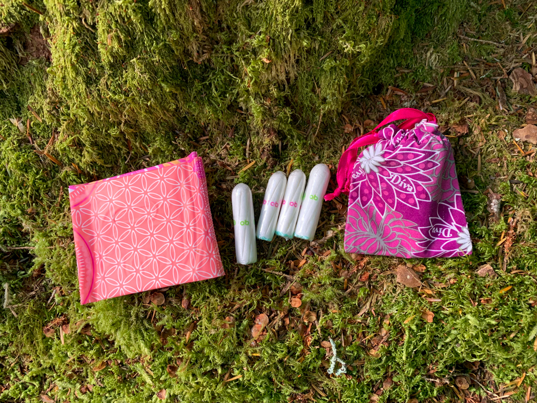 Menstrual products including pads, tampons and a cup rest on a mossy forest floor. Learn how to camp and hike on your period