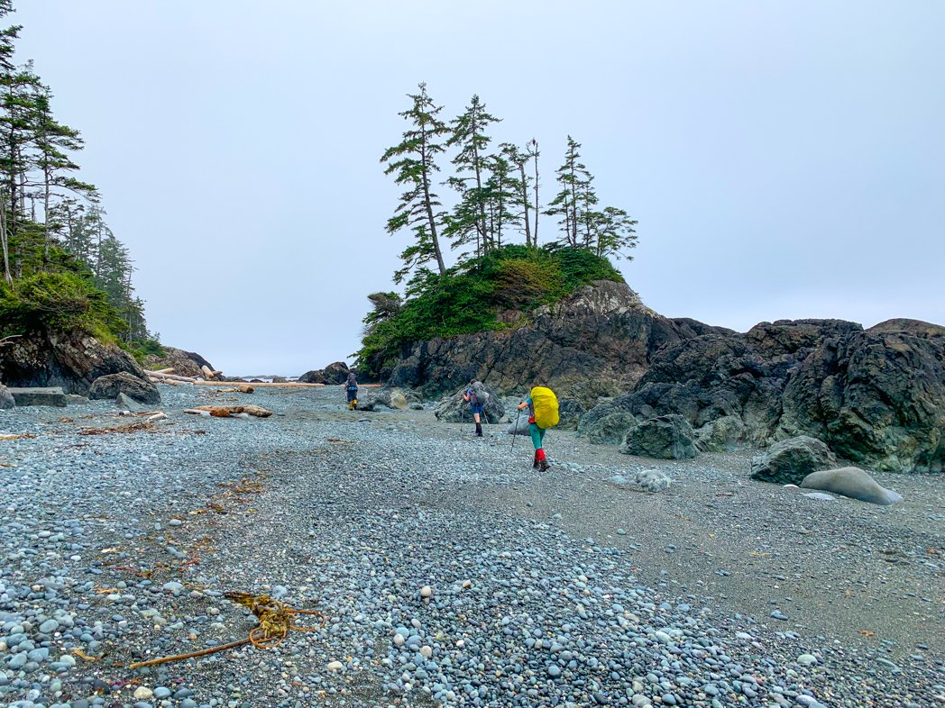 Hikers on the beach near Cape Sutil on the North Coast Trail. Day 3 of the North Coast Trail itinerary