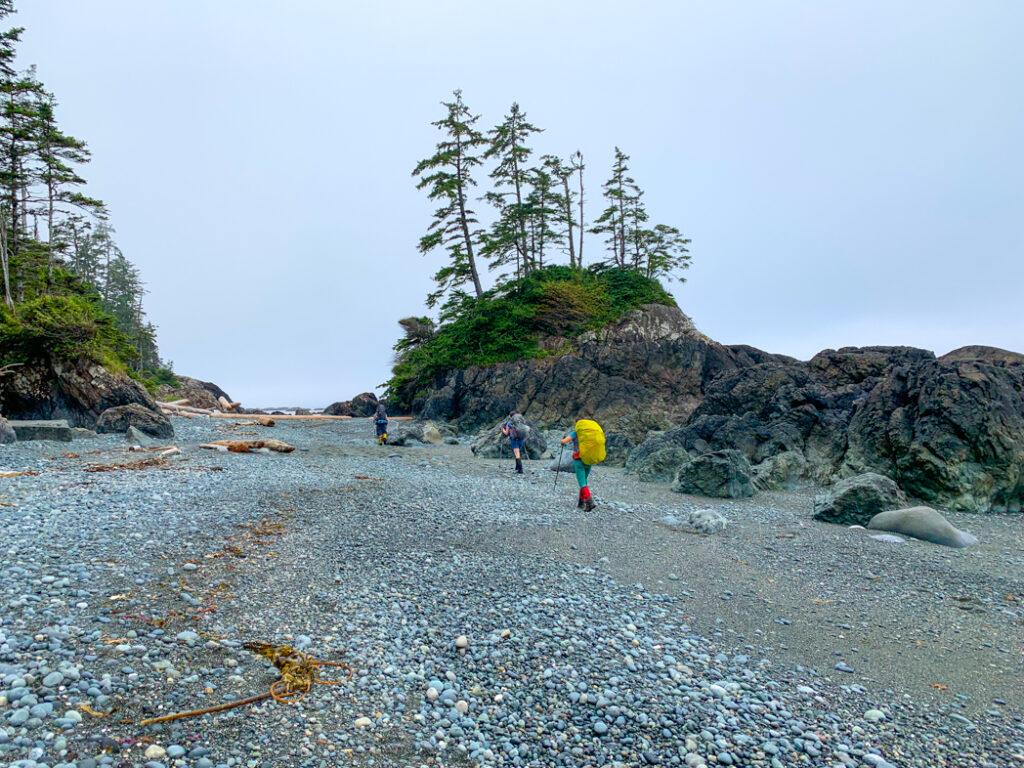 Hiking on a pocket beach on the North Coast Trail near Cape Sutil