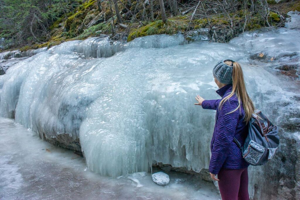 A woman next to an ice flow in Grotto Canyon in Canmore, Alberta